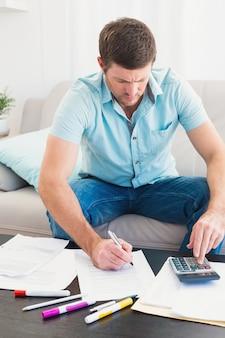 Homme concentré qui compte ses factures