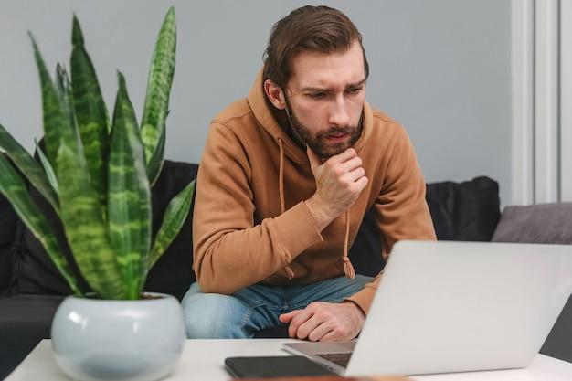 Homme concentré travaillant à la maison et regardant un ordinateur portable