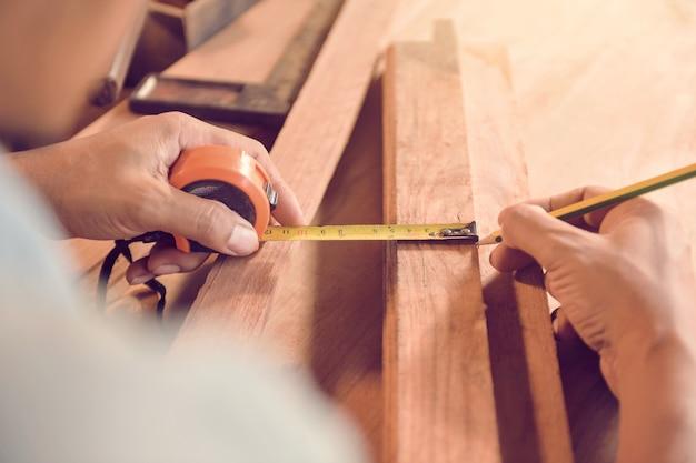 Homme avec concept de construction d'outils de charpentiers. gros plan sur un jeune charpentier masculin faisant des mesures sur la planche de bois, style vintage