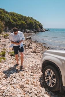 Homme de concept de voyage de voiture à la plage d'été regardant la liberté de mer