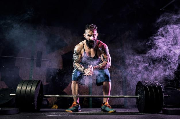 Homme de condition musculaire prépare au soulevé de terre d'une barre dans le centre de remise en forme moderne. entraînement fonctionnel.
