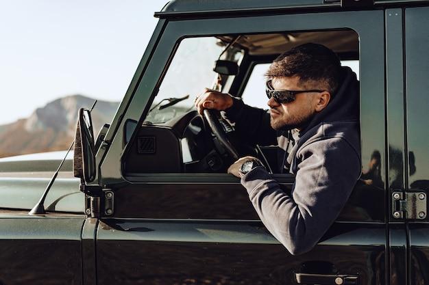 Homme conducteur d'une voiture tout-terrain regardant par la fenêtre