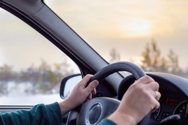 Homme conduisant une route d'hiver tôt le matin, vue intérieure