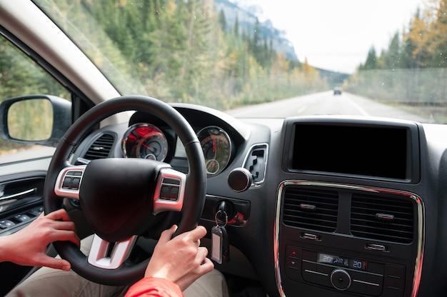 Homme conduisant une voiture sur l'autoroute dans la forêt d'automne au parc national