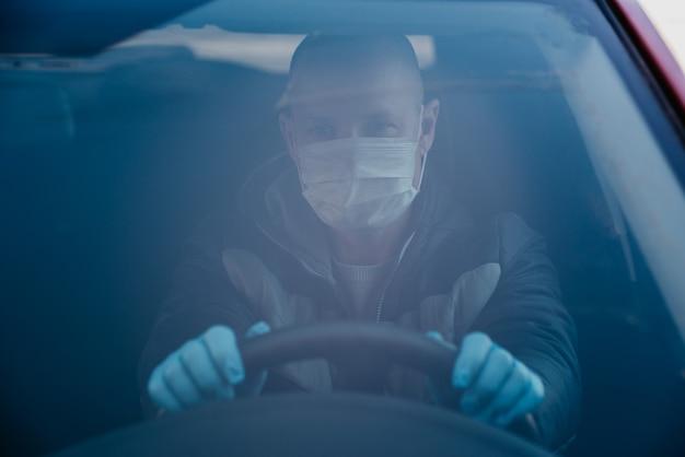 Homme conduisant une voiture dans un masque médical de protection et des gants. conduire en toute sécurité en taxi pendant la pandémie de coronavirus