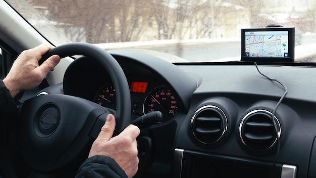 Homme conduisant une voiture dans la ville d'hiver à l'aide d'un appareil gps