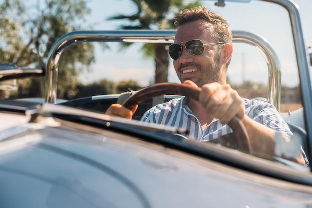 Homme conduisant une voiture d'époque convertible
