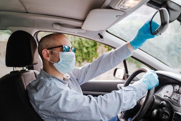 Homme conduisant une voiture portant un masque et des gants de protection lors d'une pandémie de coronacirus covid-19