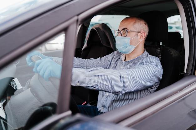Homme conduisant une voiture portant un masque et des gants de protection pendant une pandémie