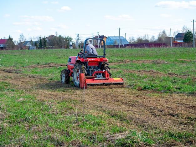 Un homme conduit un tracteur avec une tondeuse dans un champ. paillage et tonte de l'herbe. temps clair, ciel bleu. culture des terres