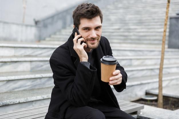 Homme confiant habillé en manteau assis à la rue de la ville, parler au téléphone mobile, montrant une tasse de café à emporter