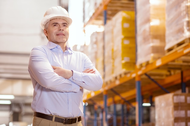 Homme confiant intelligent portant un casque tout en étant dans son entrepôt