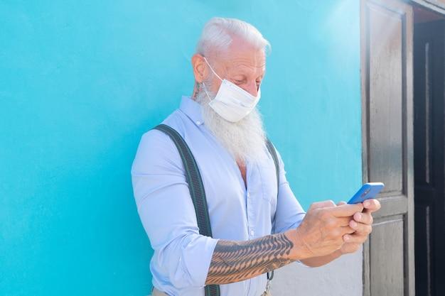 Un homme confiant senior portant un masque contre un mur bleu lors d'une épidémie de coronavirus