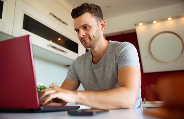 L'homme confiant et souriant moderne travaille sur l'ordinateur portable dans la cuisine domestique