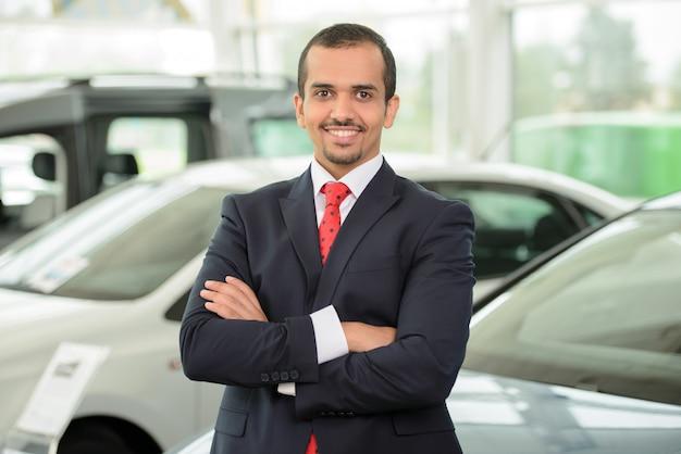 Homme confiant en vetu se penchant à la voiture.