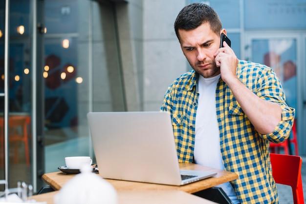 Homme confus ayant des conversations téléphoniques au café