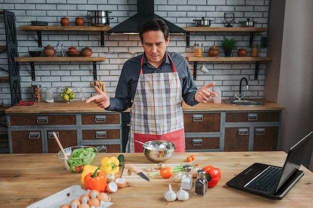 Homme confus debout à table dans la cuisine. il regarde les légumes colorés sur le bureau. l'homme porte un tablier.
