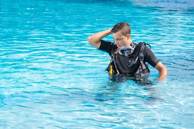 Homme confus exerçant dans la piscine avant la plongée sous-marine