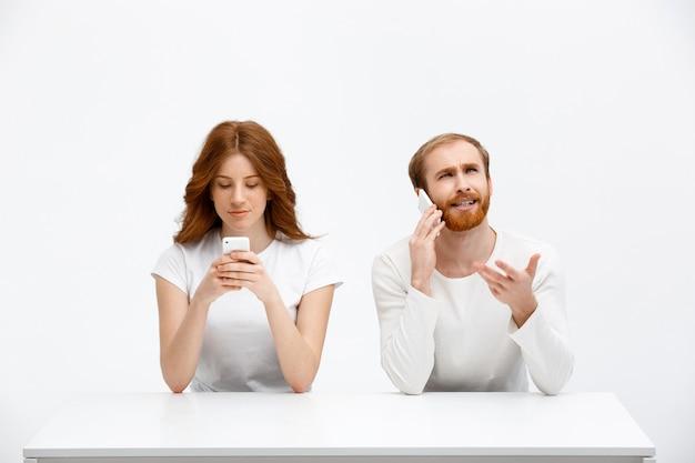 Homme confus parler téléphone, fille sourire à l'affichage mobile