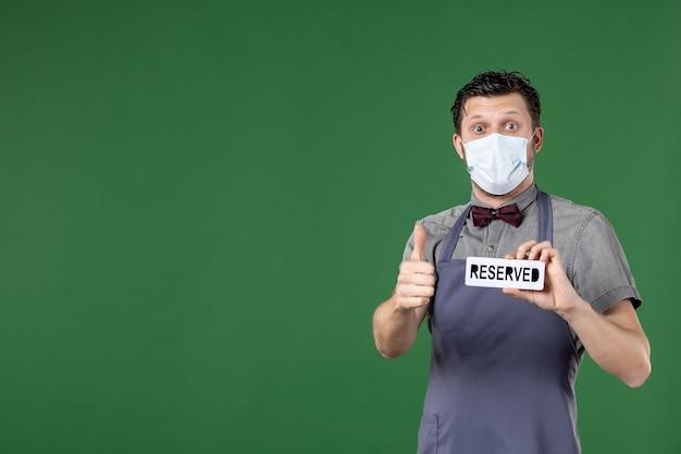 Homme confus serveur en uniforme avec masque médical et montrant une icône réservée faisant un geste correct sur fond vert