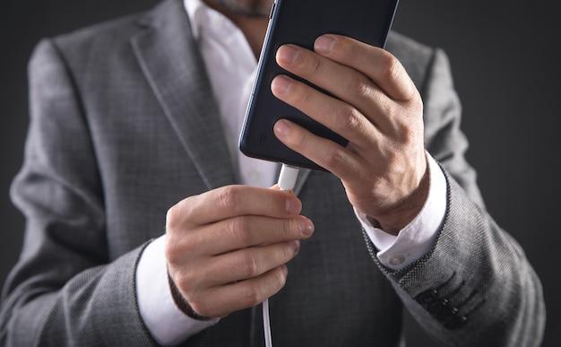 Homme connectant le câble du chargeur au téléphone portable.