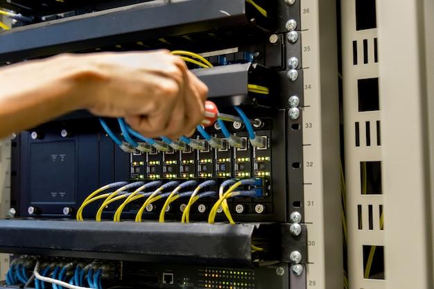 Homme connectant un câble réseau pour passer