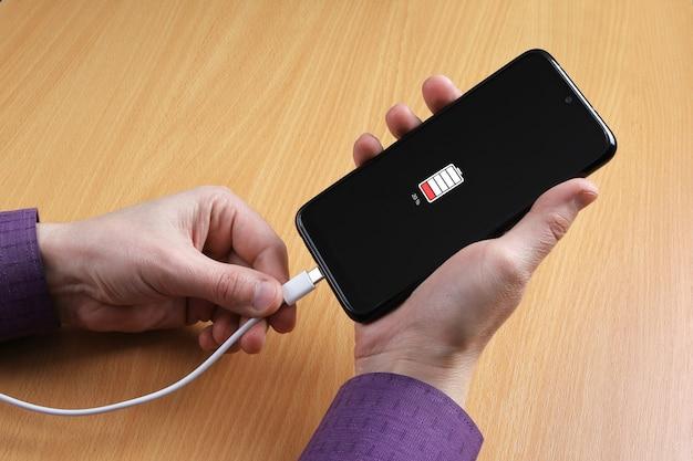 L'homme connecte le câble de charge au smartphone