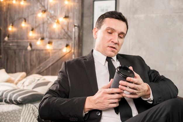 Homme considérant un verre de café en papier