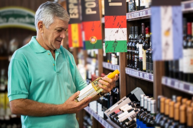 Homme de consommation choisissant des vins dans un supermarché. homme brésilien.