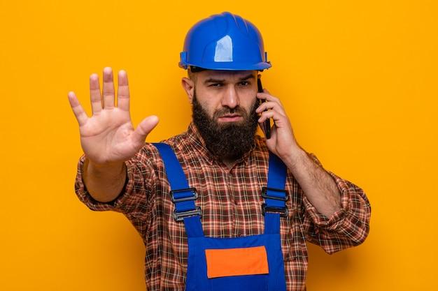 Homme constructeur barbu en uniforme de construction et casque de sécurité parlant sur téléphone portable regardant la caméra avec un visage sérieux faisant un geste d'arrêt avec la main debout sur fond orange