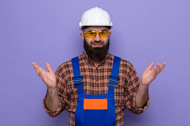 Homme constructeur barbu en uniforme de construction et casque de sécurité portant des lunettes de sécurité jaunes regardant la caméra souriant joyeusement levant les bras debout sur fond violet