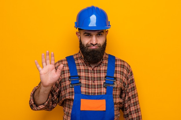 Homme constructeur barbu en uniforme de construction et casque de sécurité regardant la caméra mécontent montrant le geste d'arrêt avec la main debout sur fond orange