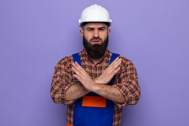 Homme constructeur barbu en uniforme de construction et casque de sécurité regardant la caméra avec un visage sérieux faisant un geste d'arrêt croisant les mains debout sur fond violet