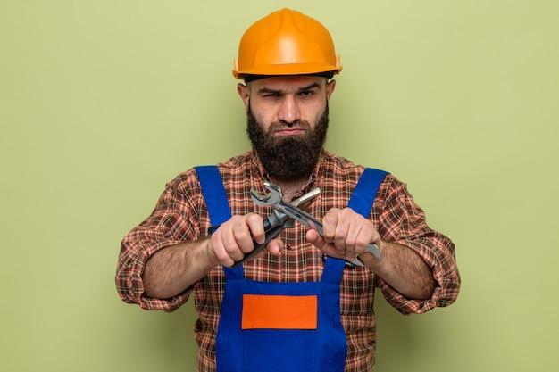 Homme constructeur barbu en uniforme de construction et casque de sécurité tenant une clé et une pince regardant la caméra avec un visage sérieux traversant les mains debout sur fond vert