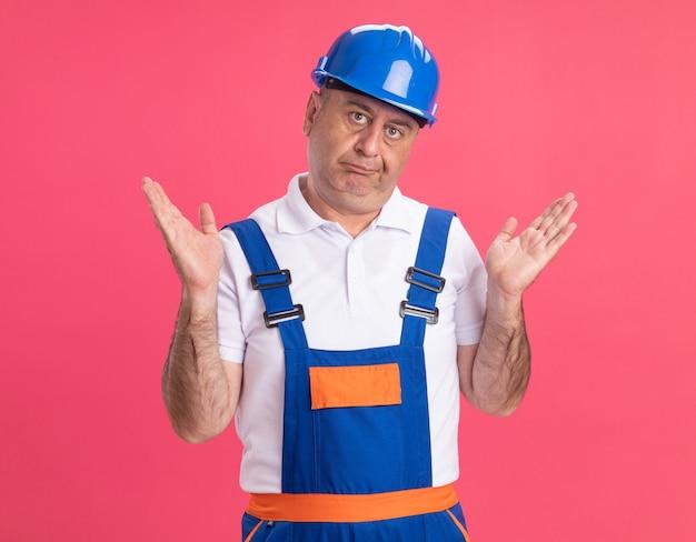 Homme de constructeur caucasien adulte confus en uniforme se tient avec les mains levées isolés