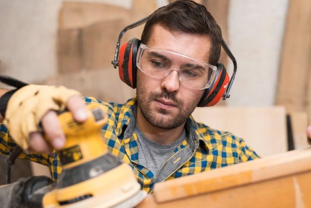 Homme constructeur charpentier polit planche de bois avec une ponceuse d'orbite aléatoire