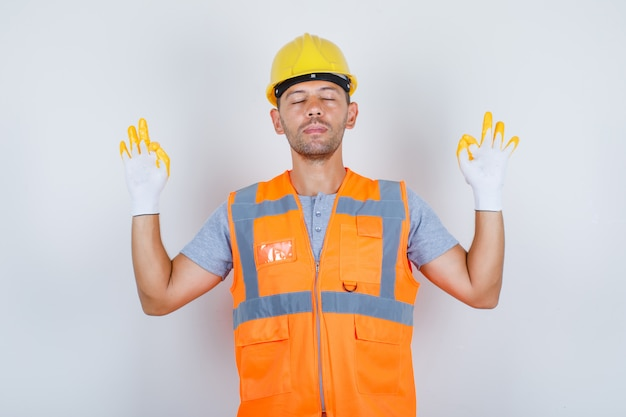 Homme constructeur faisant la méditation avec les yeux fermés en uniforme, vue de face.