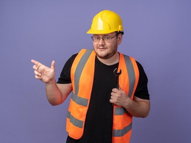 Homme de constructeur en gilet de construction et casque de sécurité regardant la caméra pointant