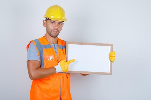 Homme constructeur montrant quelque chose sur un tableau blanc en uniforme, casque, gants vue de face.