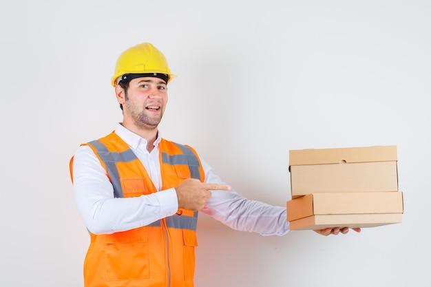 Homme de constructeur pointant le doigt sur des boîtes en carton en chemise, uniforme et à la recherche de positif. vue de face.