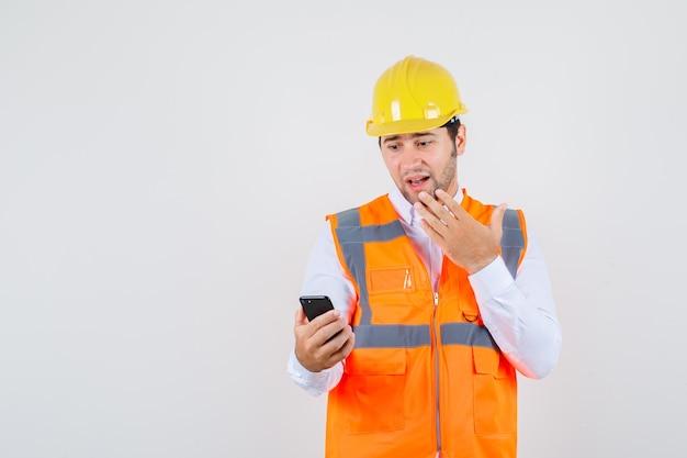 Homme de constructeur regardant smartphone avec la main sur le menton en chemise, uniforme et à la surprise. vue de face.