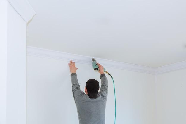 Homme constructeur rénove l'intérieur de la chambre avec un moulage en plastique