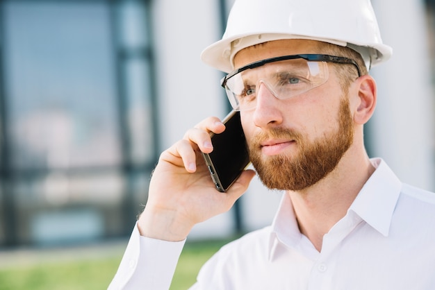Homme de constructeur avec smartphone