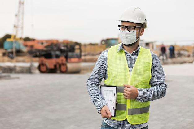 Homme de constructeur de tir moyen portant un masque