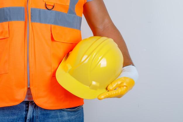 Homme constructeur en uniforme, jeans, gants tenant le casque à la main, vue de face.