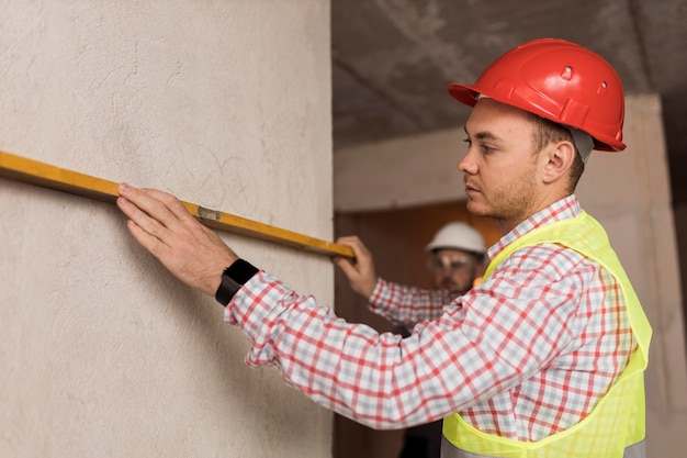 Homme de constructeur de vue latérale mesurant