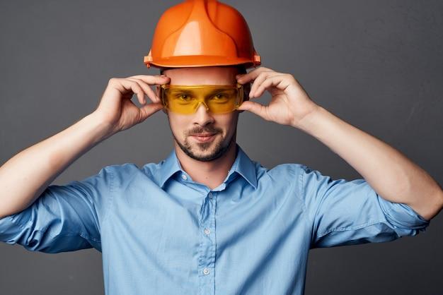 Homme en construction chemise bleue uniforme geste mains émotions travail