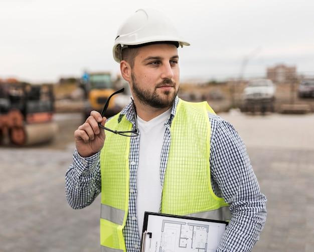 Homme de construction de coup moyen tenant des lunettes