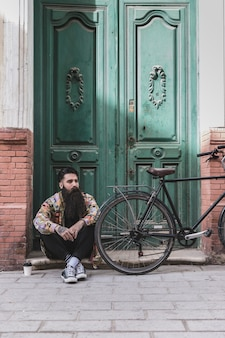 Homme contemplé assis devant une vieille porte avec sa bicyclette