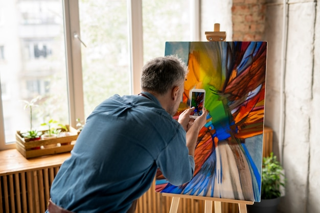 Homme contemporain avec smartphone debout devant des œuvres d'art sur chevalet et prendre une photo de la peinture